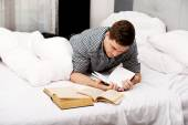 Thoughtful man with a book in his bed. — Stock Photo