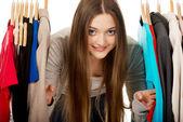 Teen woman between clothes on hanger. — Stock Photo