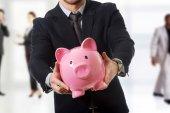 Businessman holding a piggybank. — Stock Photo