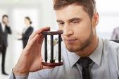 Businessman holding hourglass. — Stock Photo