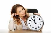 Businesswoman with clock by a desk. — Stock Photo