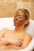 Woman relaxing in bath with chocolate mask on face — Stock Photo