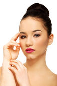Woman with full make up touching face. — Stock Photo