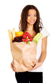 Young woman with grocery and vegetables. — Stock Photo