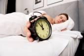 寝室の目覚まし時計を持つ男. — ストック写真