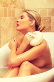 Woman relaxing in a bath and washing herself — Stock Photo