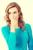 Portrait of a woman clogging nose — Stock Photo