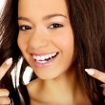 Beautiful woman pointing to teeth. — Stock Photo #74782669