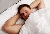 Handsome young man lying in bed. — Stock Photo