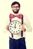 Man wearing suspenders holding big clock. — Stock Photo