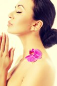 Woman with purple orchid petal on shoulder — Stock Photo