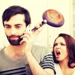 Angry young woman hitting men with frying pan. — Stock Photo #75683885