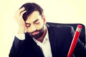 Tired businessman writing in the office — Stock Photo