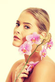 Spa woman with purple orchid — Stock Photo