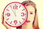Aantrekkelijke jonge vrouw in de gele boven houden een klok. — Stockfoto
