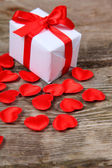 Holidays gift and red hearts on wooden background.  — Stock Photo