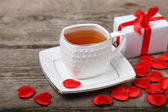Cup of tea, gift and red hearts  — Stock Photo