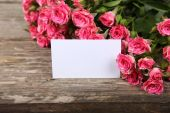 Pink roses and greeting card — Stock Photo