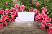 Bouquet of pink roses, heart  and greeting card — Stock Photo