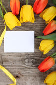 Bouquet of tulips and greeting card — Stock Photo