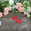 Bouquet of of beautiful flowers and red hearts — Stock Photo #68577095