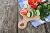 Cucumbers and tomatoes on a cutting board — Stock Photo