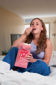 Woman in bed with popcorn — Stockfoto