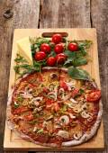 Delicious pizza on the wooden table — Photo