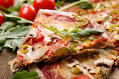 Delicious pizza on the wooden table — Stockfoto