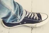 Leg in classic sneakers — Stock Photo