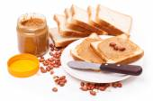 Peanut butter with heap of peanuts — Stockfoto