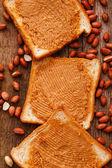 Peanut butter cream on a toast — Stock Photo