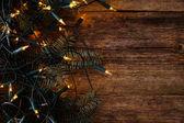 Abeto con guirnalda en una mesa de madera — Foto de Stock