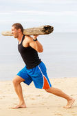 Bodybuilder with wood on the beach — Stock Photo