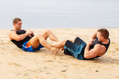 Bodybuilders during workout on the beach — Stock Photo