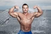 Bodybuilder with sexy body on the beach — Stock Photo