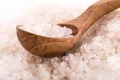 Heap of sea salt with wooden spoon — Stock Photo