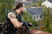 Soldier with a gun on roof — Stock Photo