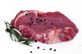 Raw steak with branch of rosemary and peppercorn — Stock Photo