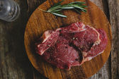 Raw steak with rosemary and peppercorn — Stock Photo