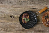 Grilled steak with rosemary in tray — Stock Photo