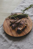 Grilled steak with branch of rosemary — Stock Photo