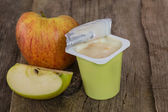 Yoghurt with halves of apple — Stock Photo