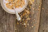 Yoghurt with muesli and spoon — Stock Photo