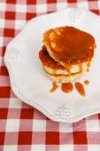 Pancakes with caramel on white plate — Stock Photo
