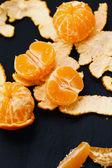 Shelled mandarins on black — Stock Photo