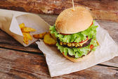 Delicious burger on the wooden table — Stock Photo