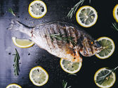 Fish with lemon on the wooden table — Stock Photo