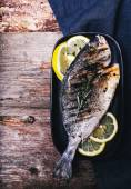 Grilled fish with lemon on the wooden table — Stock Photo