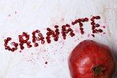 Juicy pomegranate  and word granate — Stockfoto